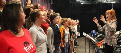 Photo of Laura leading Sing City choir
